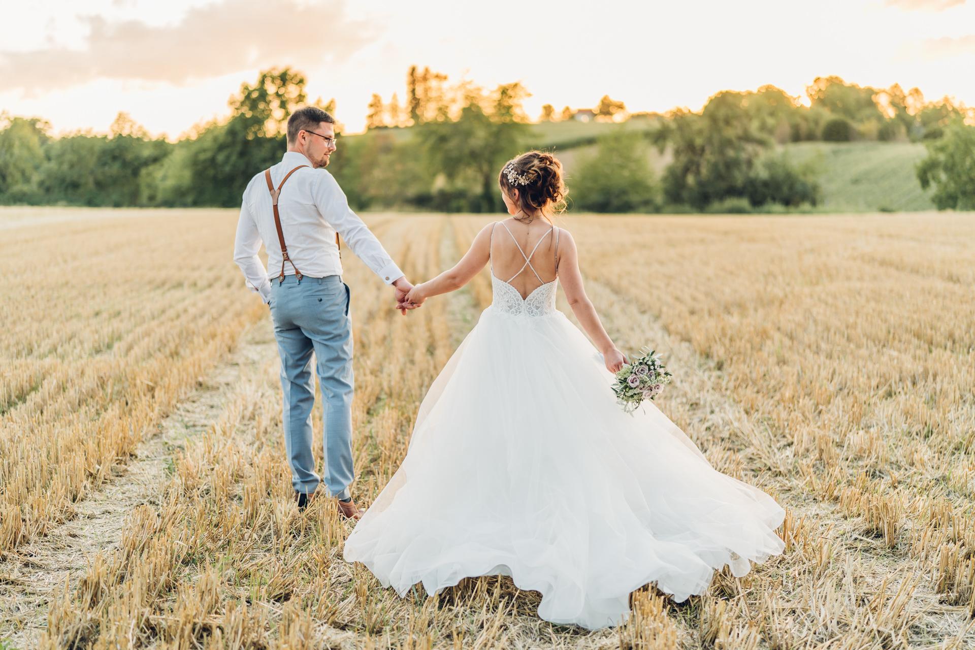 Hochzeitsfoto von einem Brautpaar bei der Burg Schwarzenstein. Braut und Bräutigam gehen Hand in Hand Richtung Sonnenuntergang