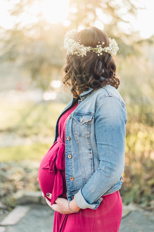 Natürliche Babybauchbilder in der untergehenden Sonne mit Blumenkranz