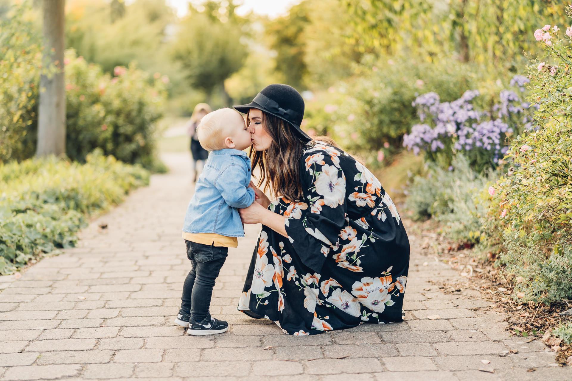 Hübsche junge Mama im Blumenkleid küsst ihren kleinen Sohn in der Natur im Sonnenuntergang
