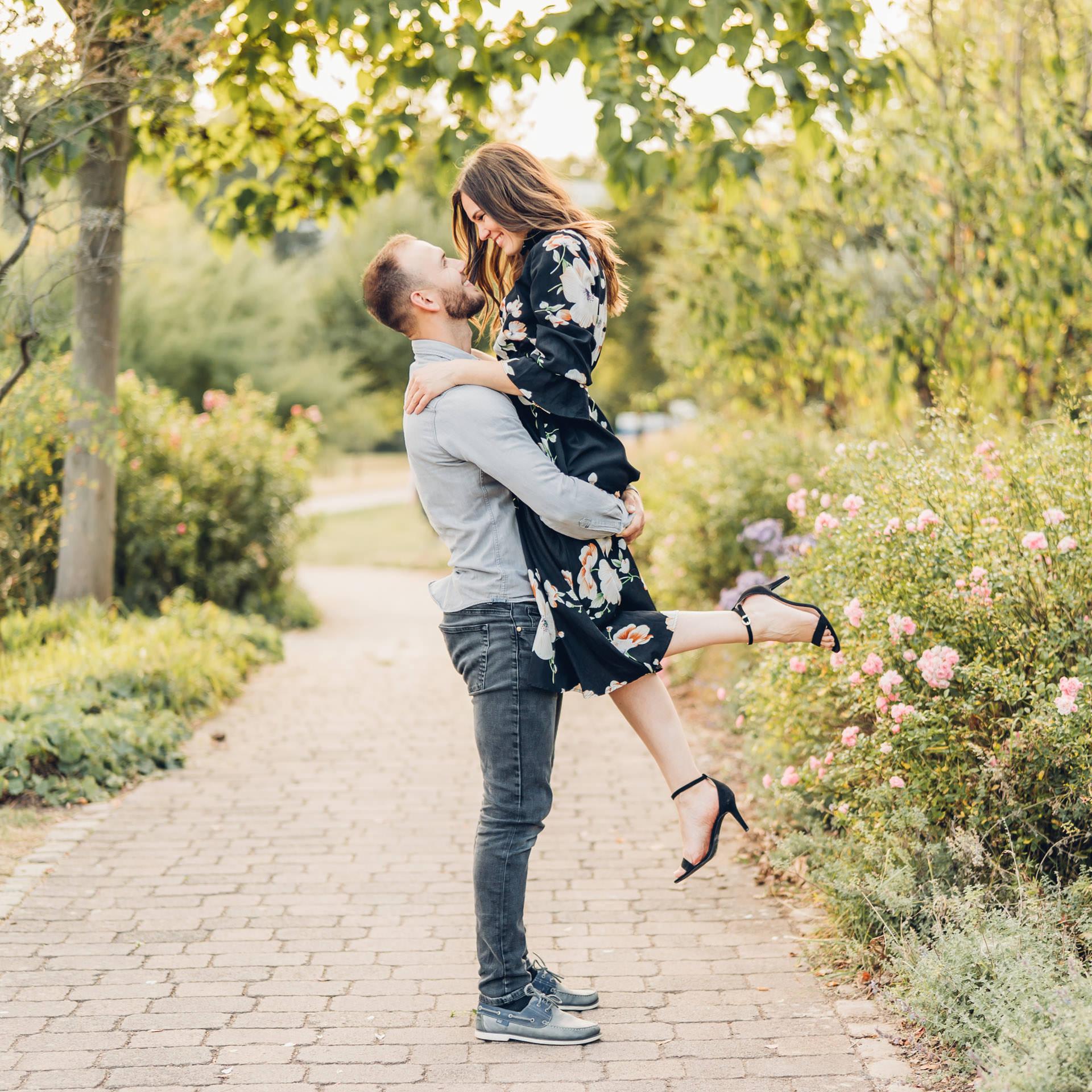 Jungre Mann hebt seine dunkelhaarige hübsche Frau hoch bei einem Verlobungsshooting Mainz