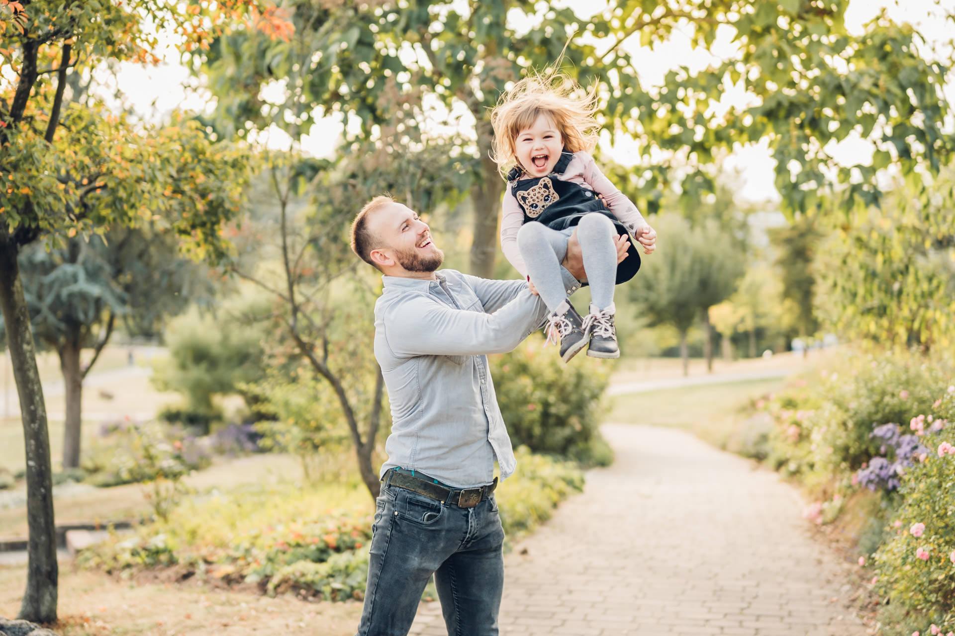 Junger Papa wirft seine kleine lachende Tochter in die Luft