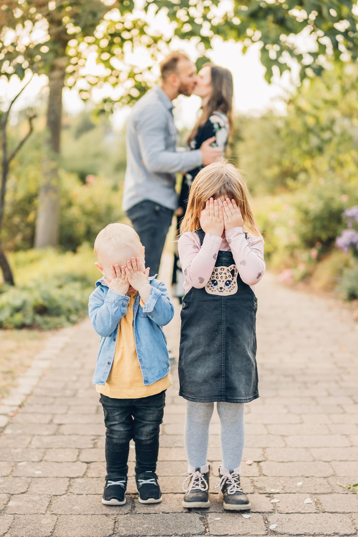 Kinder halten sich die Augen zu während sich das Paar, ihre Eltern, im unscharfem Hintergrund bei Sonnenuntergang küssen