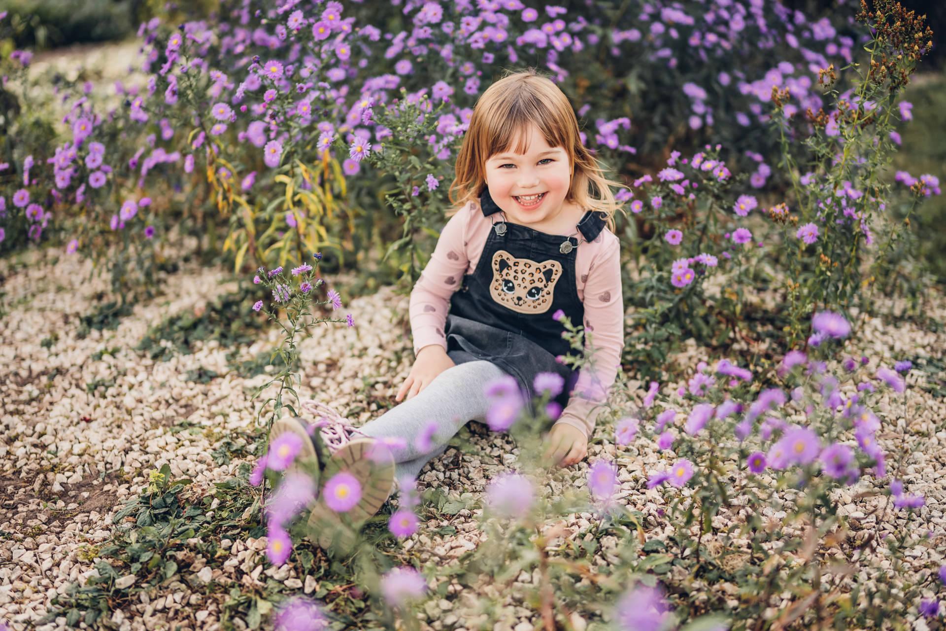 Kinderfoto Mädchen in einer lila Blumenwiese im Strecktal Park in Pirmasens