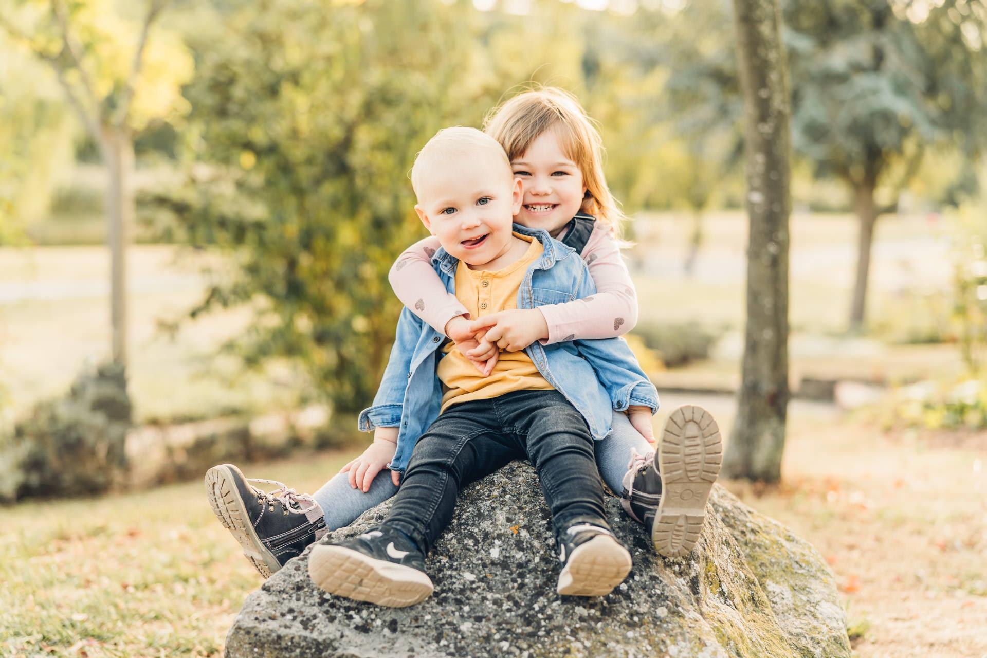 Geschwister Mädchen und Junge umarmen sich beim Familienfotograf in Rheinland Pfalz