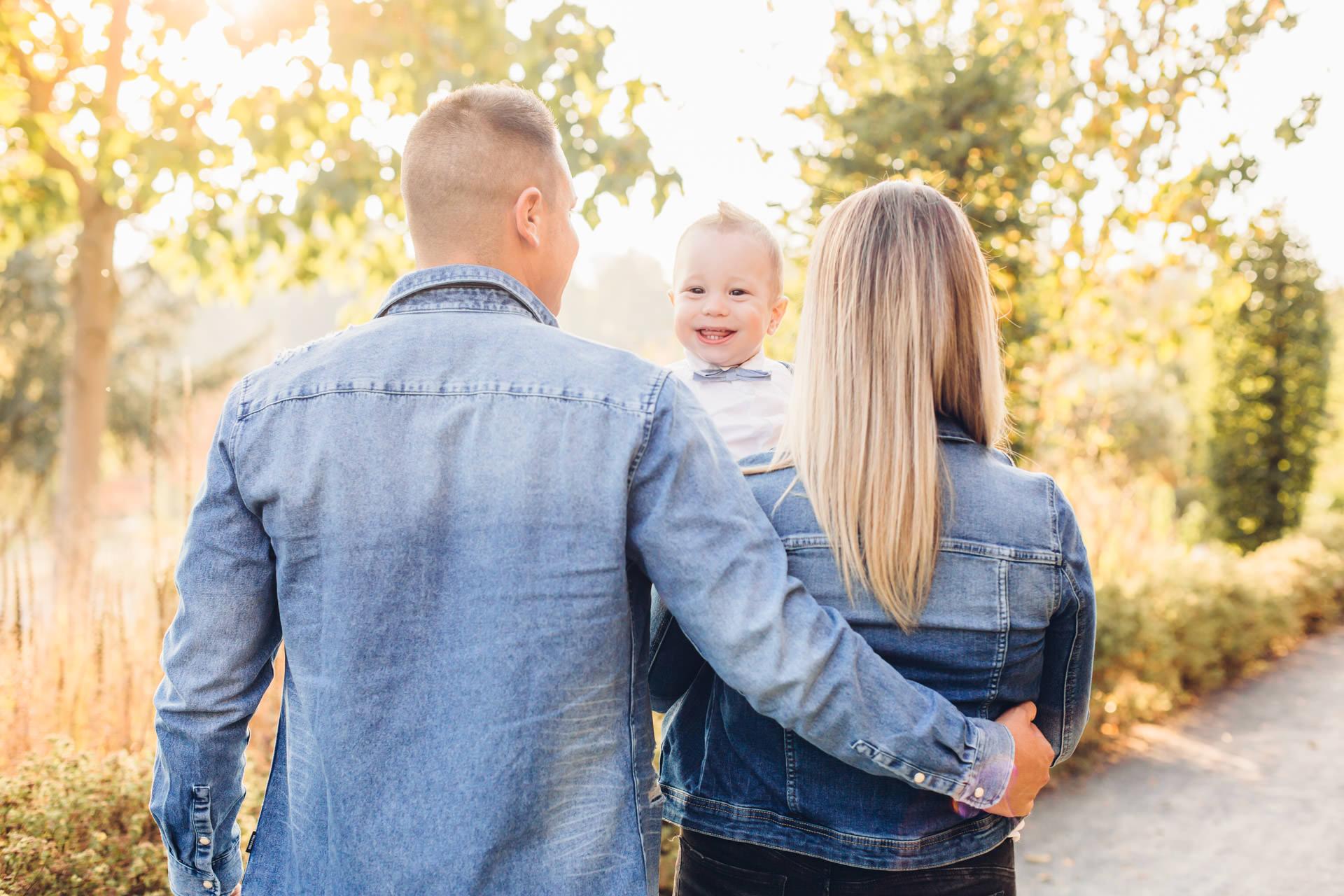 Familienfotos zum ersten Geburtstag kleiner Junge schaut über die Schulter