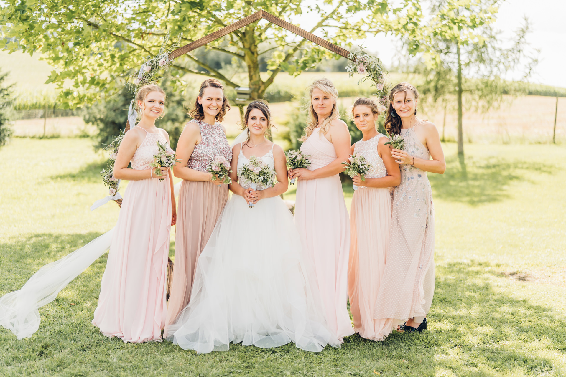 Braut mit ihren Brautjungfern in hellrosa Kleider