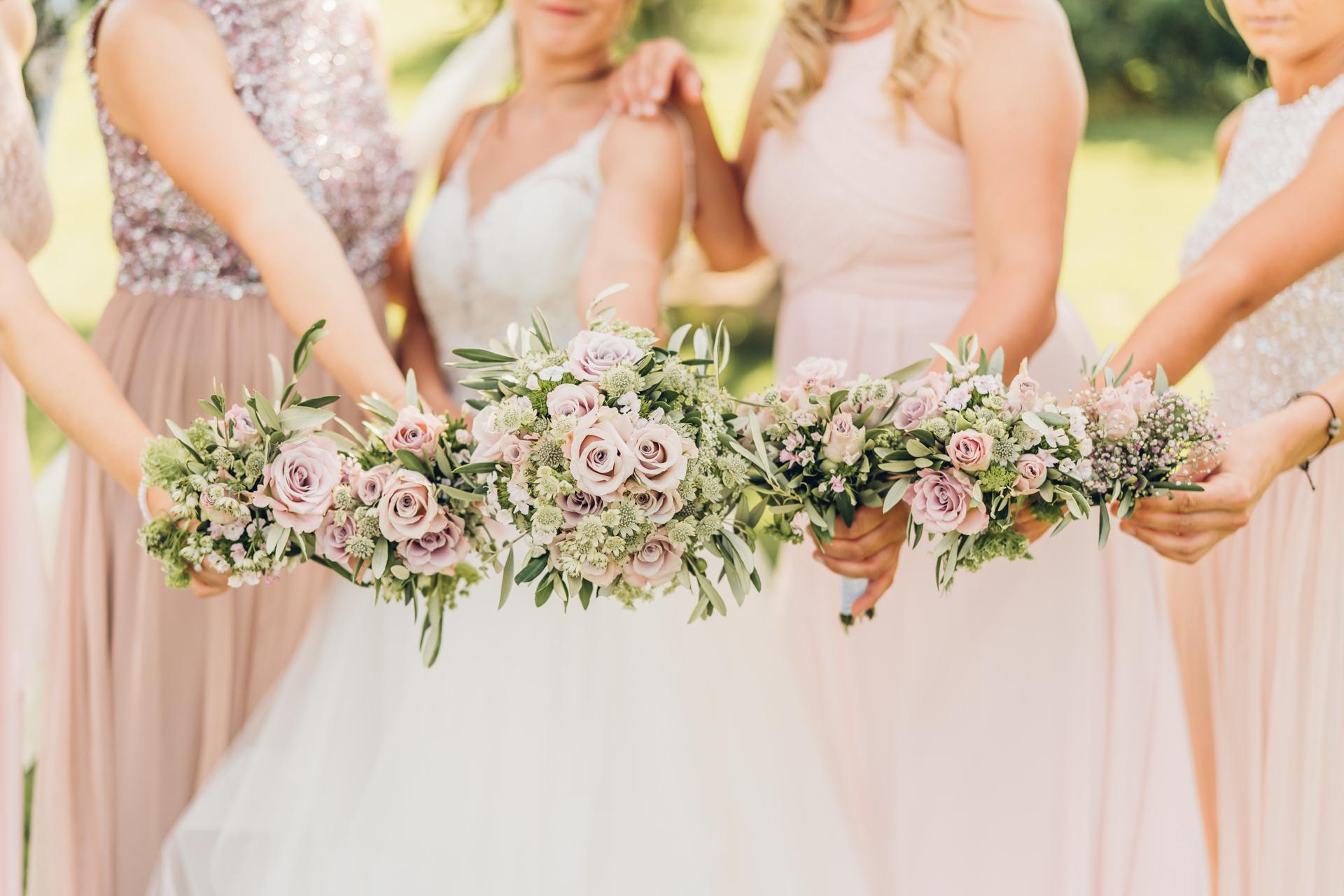 Braut mit Brautjungfern und Blumensträußen