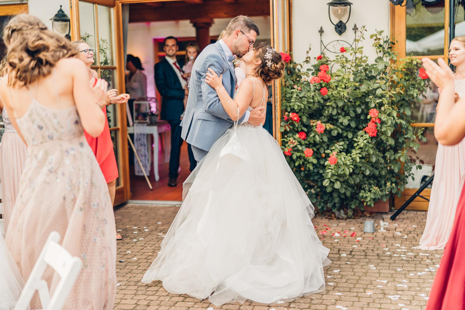 Brautpaar küsst sich auf Hochzeitsfeier am Weingut Höflich