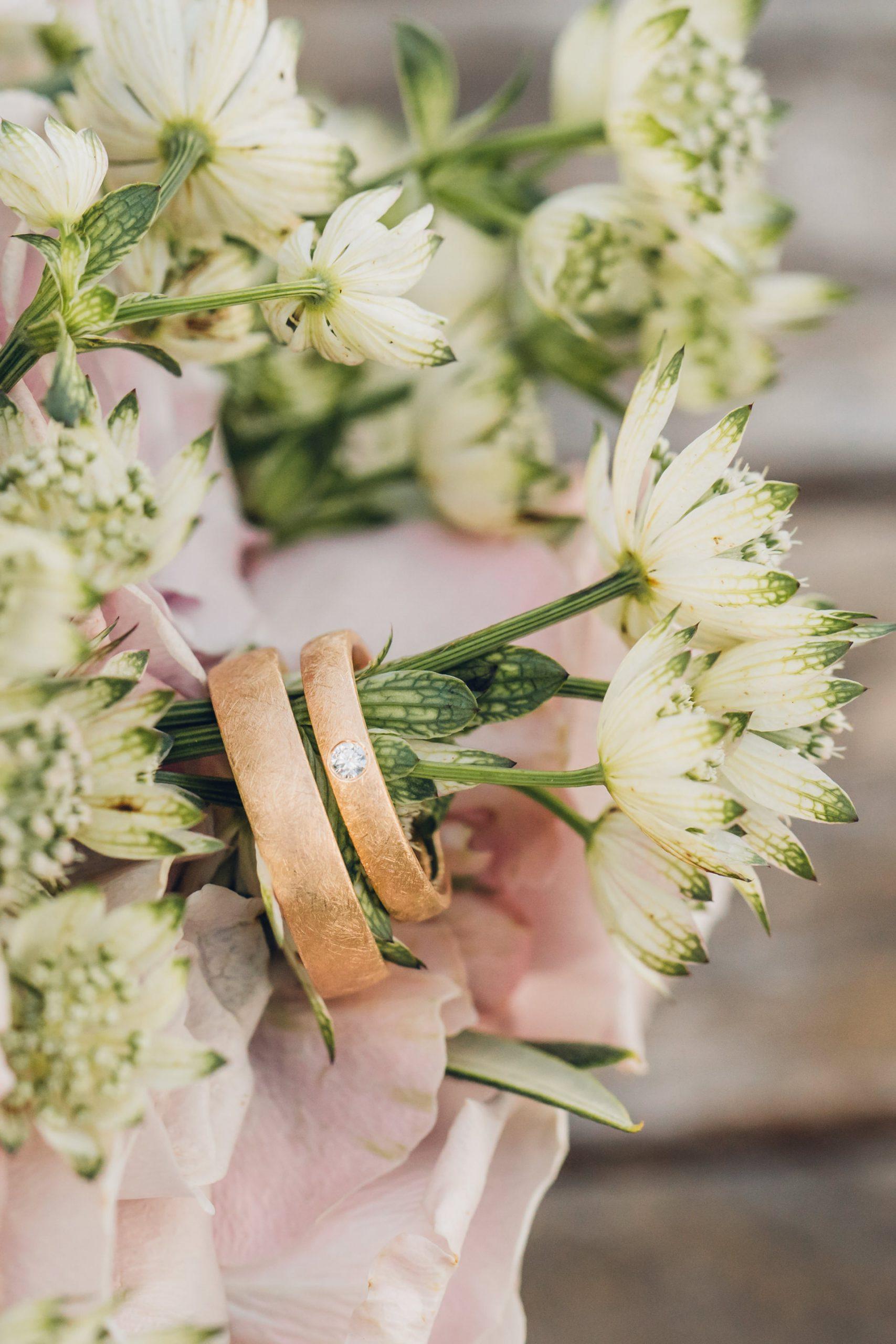 Hochzeitsringe und Blumen Detailfoto