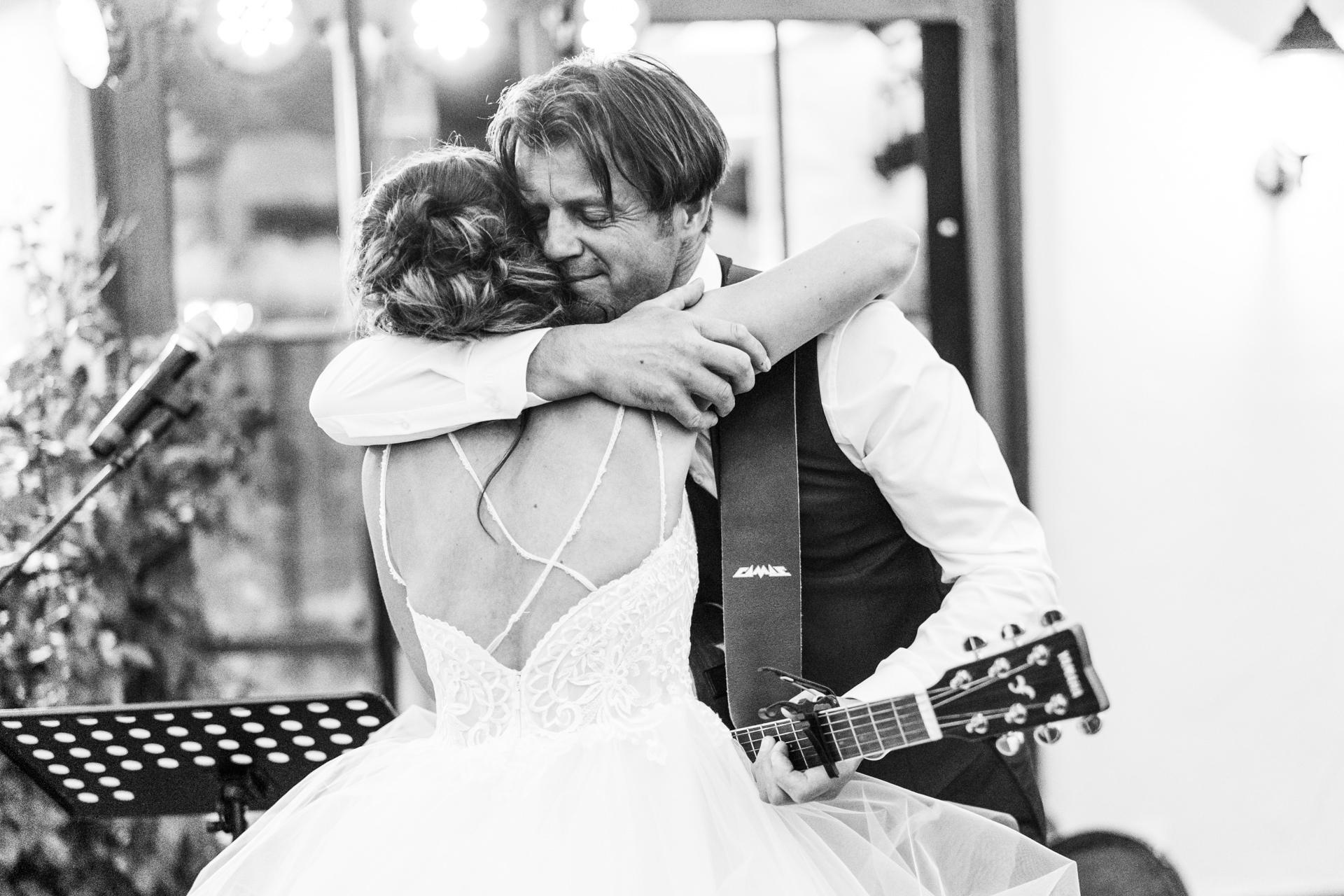 Braut und Brautvater bei emotionaler Umarmung am Hochzeitstag